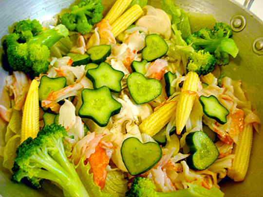 A bowl of salad containing star-shaped and heart-shaped cucumber slices