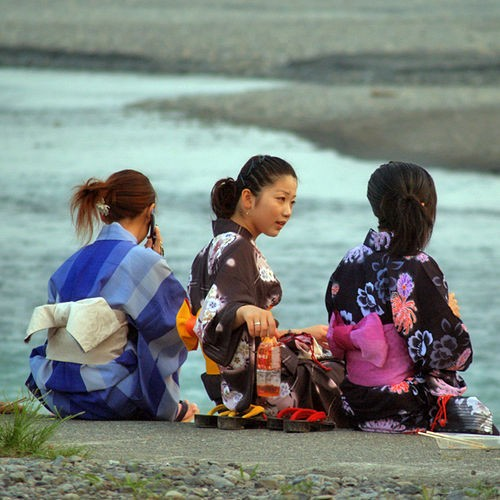 Three girls wearing yukata at a beach-side fireworks display in Shizuoka City