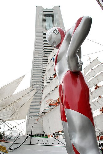 A giant replica of Ultraman stands in front of the Nippon Maru sailing boat and Landmark Tower in Yokohama